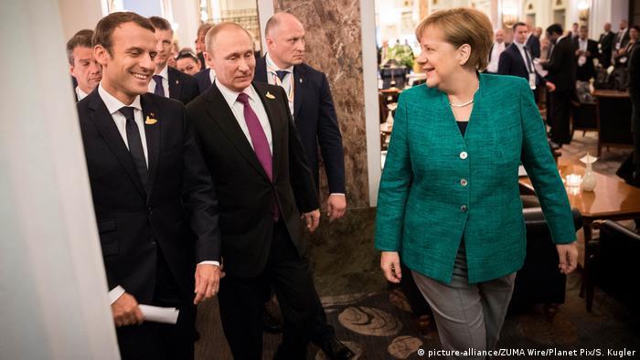 German Chancellor Angela Merkel smiling towards Russian President Vladimir Putin and French President Emmanuel Macron