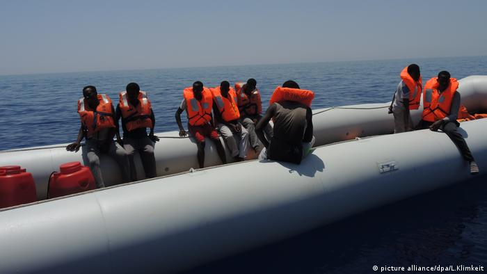Migrants sitting in rubber dinghy (picture alliance/dpa/L.Klimkeit)