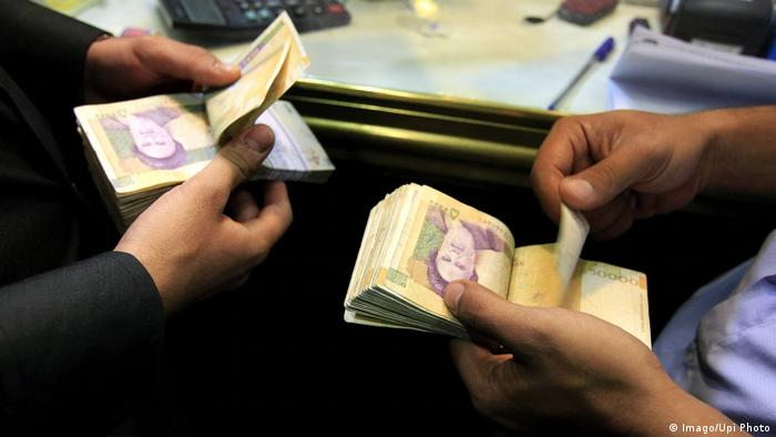 Men count Iranian banknotes