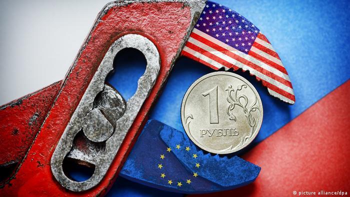 Рубль зажат в плоскогубцах с изображением флагов ЕС и США
