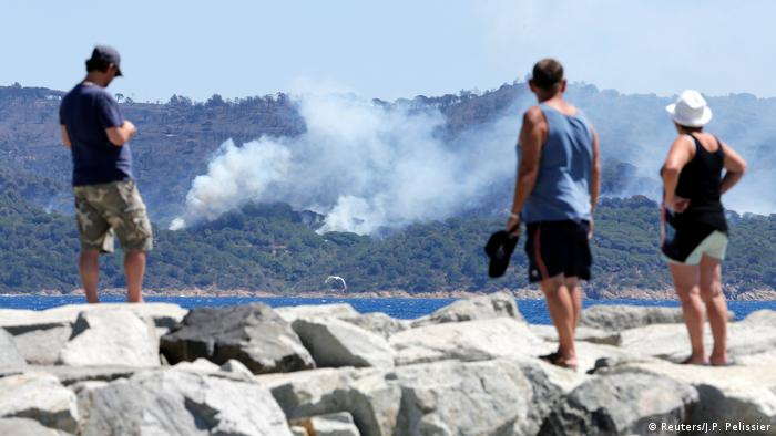 Three Saint-Tropez tourists look at the burning forest across the bay (Reuters/J.P. Pelissier)