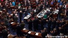 A still image from video shows U.S. Senator John McCain (R-AZ), who had been recuperating in Arizona after being diagnosed with brain cancer, acknowledging applause as he arrives on the floor of the U.S. Senate after returning to Washington for a vote on healthcare reform in Washington, U.S., July 25, 2017. SENATE TV/Handout via REUTERS THIS IMAGE HAS BEEN SUPPLIED BY A THIRD PARTY.