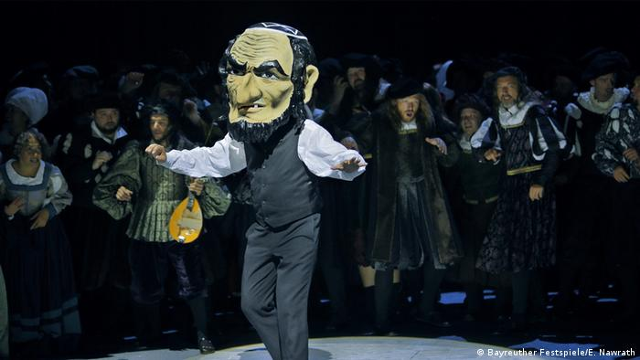 Man wearing a grotesque mask parades onstage