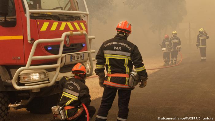 Firefighters stand in smoke next a fire truck (picture-alliance/MAXPPP/D. Leriche)