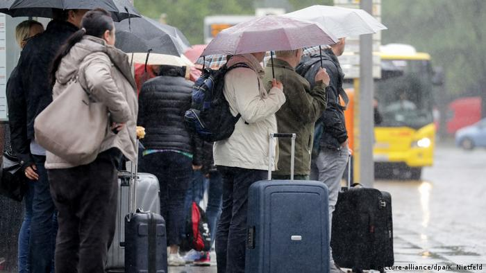 Travellers with suitcases waiting in the rain at a Berlin bus station