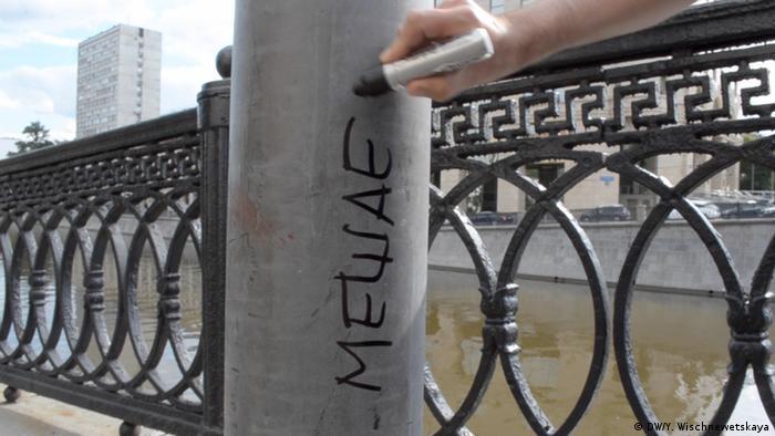 Надпись Мешает на столдбе, который находится на тротуаре