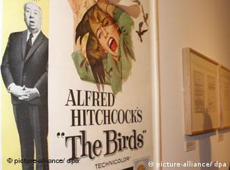 Alfred Hitchcock with a poster advertizing The Birds