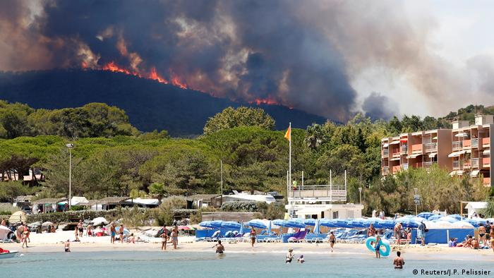 Flames and smoke fill the sky above a burning hillside as tourists swim on the beach in Bormes-les-Mimosas, France, July 26 (Reuters/J.P. Pelissier)