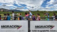 25.07.2017 TOPSHOT - Venezuelan citizens cross the Simon Bolivar international bridge from San Antonio del Tachira, Venezuela to Cucuta, Norte de Santander Department, Colombia, on July 25, 2017. Some 25.000 Venezuelans cross to Colombia and return to their country daily with food, consumables and money from ilegal work, according to official sources. Also, there are 47.000 Venezuelans in Colombia with legal migratory status and another 150.000 who have already completed the 90 allowed days and are now without visa. / AFP PHOTO / Luis Acosta (Photo credit should read LUIS ACOSTA/AFP/Getty Images)