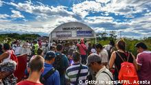 25.07.2017 Venezuelan citizens queue to cross the Simon Bolivar international bridge from San Antonio del Tachira, Venezuela to Cucuta, Norte de Santander Department, Colombia, on July 25, 2017. Some 25.000 Venezuelans cross to Colombia and return to their country daily with food, consumables and money from ilegal work, according to official sources. Also, there are 47.000 Venezuelans in Colombia with legal migratory status and another 150.000 who have already completed the 90 allowed days and are now without visa. / AFP PHOTO / Luis Acosta (Photo credit should read LUIS ACOSTA/AFP/Getty Images)
