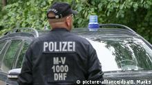 Einsatzkräfte der Polizei stehen am 26.07.2017 vor einem Mehrfamilienhaus in Boldebuck (bei Güstrow, Mecklenburg-Vorpommern). Die Polizei hat am Mittwoch mehrere Objekte in Güstrow und Umgebung (Landkreis Rostock) im Rahmen eines Antiterroreinsatzes durchsucht. Foto: Bodo Marks/dpa +++(c) dpa - Bildfunk+++ | Verwendung weltweit