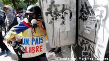 A demonstrator makes a fake call using a public phone at a rally during a strike called to protest against Venezuelan President Nicolas Maduro's government in Caracas, Venezuela July 26, 2017. On his vest reads I want a free country. REUTERS/Andres Martinez Casares