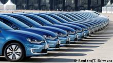 FILE PHOTO: People walk past a row of Volkswagen e-Golf cars during the company's annual news conference in Berlin, Germany March 13, 2014. Picture taken March 13, 2014. REUTERS/Tobias Schwarz/File Photo