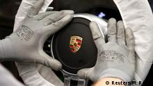 FILE PHOTO: A worker assembles a steering wheel of a new Porsche 911 sports car at the Porsche factory in Stuttgart-Zuffenhausen, March 10, 2015. REUTERS/Michaela Rehle TPX IMAGES OF THE DAY/File Photo