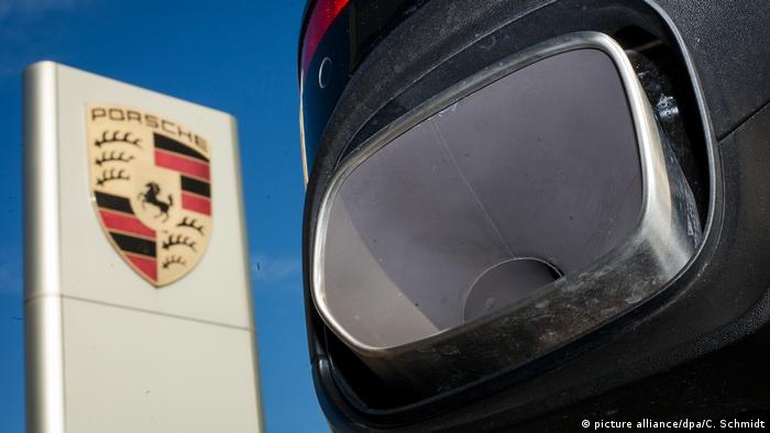 The logo of carmaker Porsche next to an exhaust pipe of a Porsche Cayenne