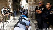 Palestinian men pray as Israeli security forces secure outside the compound known to Muslims as Noble Sanctuary and to Jews as Temple Mount, in Jerusalem's Old City July 26, 2017. REUTERS/Ronen Zvulun TPX IMAGES OF THE DAY