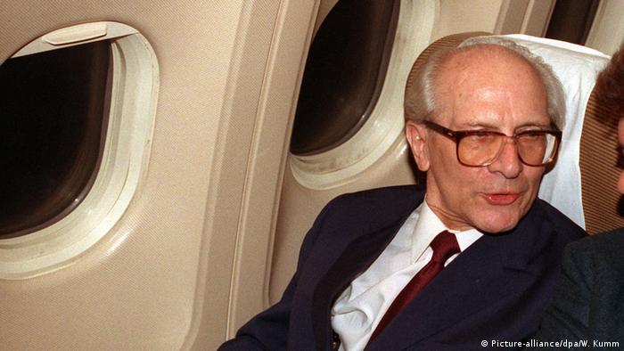 Homem grisalho de óculos sentado junto à janela em avião