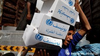 An aid worker carrying hygiene kits in Sanaa