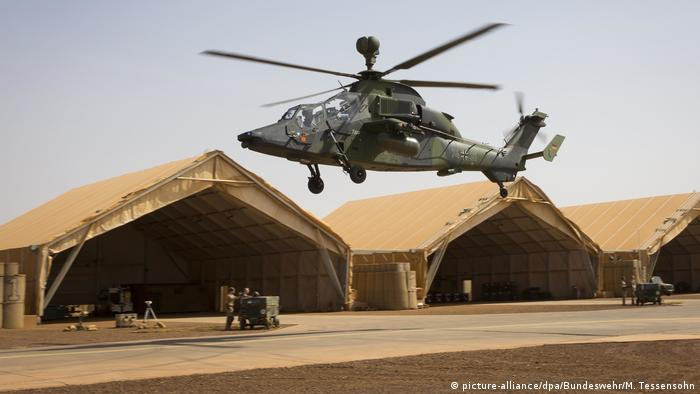 A German Tiger helicopter hovers in front of tent-like hangers at Gao