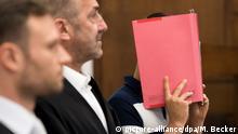 21.07.2017 ARCHIV- Der 29-jährige Angeklagte steht am 21.07.2017 im Landgericht in Köln (Nordrhein-Westfalen) neben seinen Verteidigern Alexander Paradissis (l) und Markus Bündgens (M) hinter der Anklagebank. Die Staatsanwaltschaft wirft dem 29-Jährigen versuchte gewerbsmäßige Computersabotage vor. Als Folge waren bei rund 1,25 Millionen Telekom-Kunden teilweise Internet, Telefon und Fernsehen gestört. Foto: Marius Becker/dpa +++(c) dpa - Bildfunk+++ | Verwendung weltweit