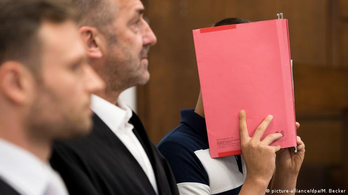 A man standing next to a lawyer, covering his face with a folder