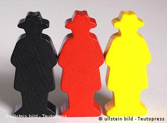 Three wooden figures in black, red and gold