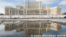 Der Palast des Parlaments spiegelt sich am 24.01.2017 in der rumänischen Hauptstadt Bukarest in einer Pfütze wieder. Der Parlamentspalast ist eines der flächenmäßig größten Gebäude der Welt. Foto: Christoph Schmidt/dpa | Verwendung weltweit