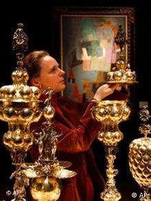 A woman looks at a rare German parcel-gilt Bodendik table fountain, circa 1630 in front of a painting by Pablo Picasso