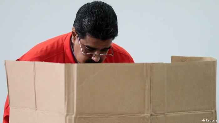 President Maduro polling behind a brown cardboard screen(Reuters)