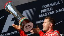 Formula One - F1 - Hungarian Grand Prix - Budapest, Hungary - July 30, 2017 Ferrari's Sebastian Vettel celebrates winning the race on the podium with the trophy REUTERS/Laszlo Balogh