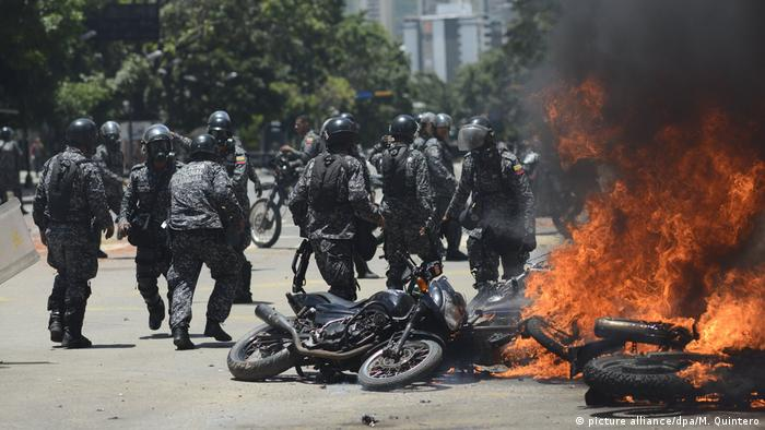 Police next to burning motorbikes in Caracas