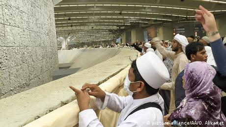 Pilgrims throw stones at a wall to symbolize the stoning of the devil.