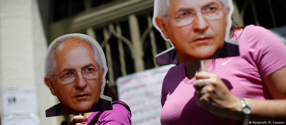 Manifestantes com imagens do líder opositor Antonio Ledezma, preso durante a madrugada