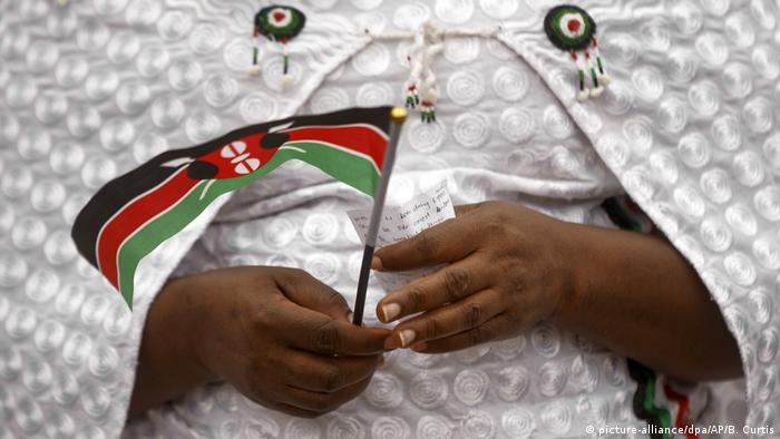 A woman holding a small Kenyan flag