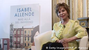 Isabel sitzt neben einem Plakat mit dem Cover ihrer neusten Novelle