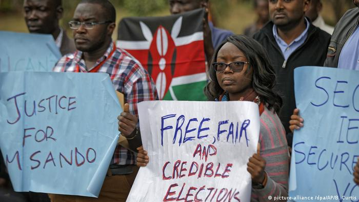 Protesters in Nairobi holding signs to protest the murder of Christopher Msando (picture-alliance /dpa/AP/B. Curtis)