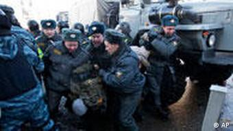 Police officers detain a demonstrator during a protest in central Moscow,