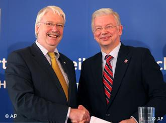 Roland Koch (CDU) and Joerg-Uwe Hahn of the Free Democratic Party FDP, shake hands during a news conference in Wiesbaden