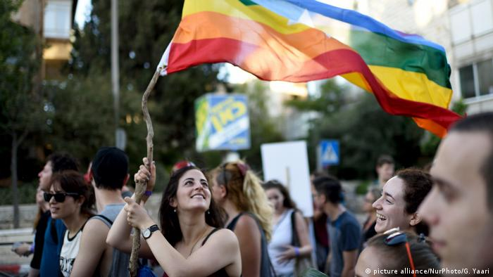 A woman holds a rainbow flag at Gay pride Parade in Jerusalem