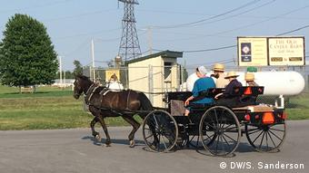 An Amish family rides in a horse-drawn carriage