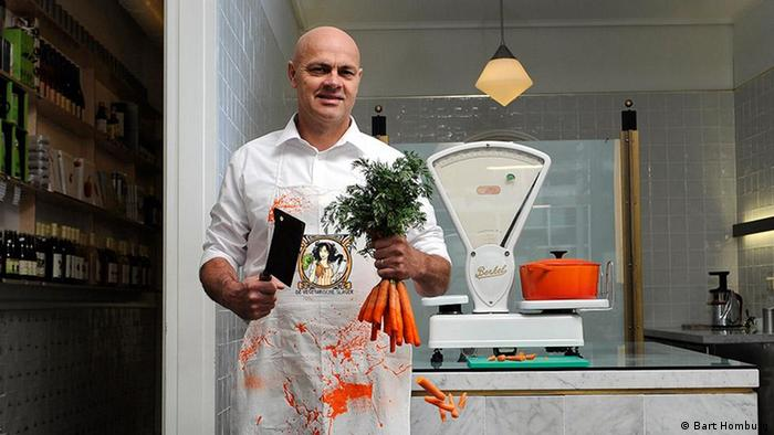 Jaap Korteweg, the vegetarian butcher, standing in his store: He holds a bunch of carrots and a knife in his hand