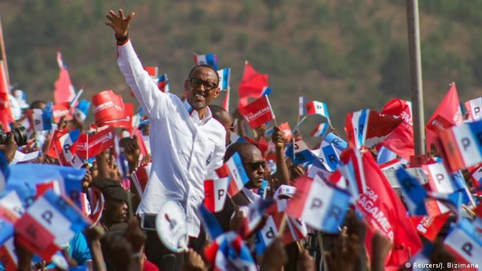 Paul Kagame raises his had to a cheering crowd waving flags