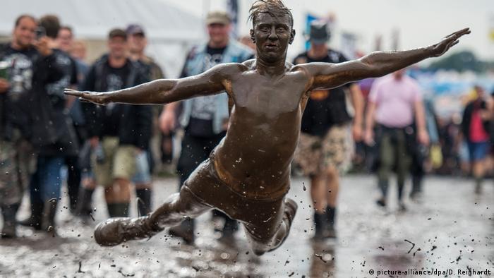 Con sus brazos abiertos, un hombre salta a un charco de barro.