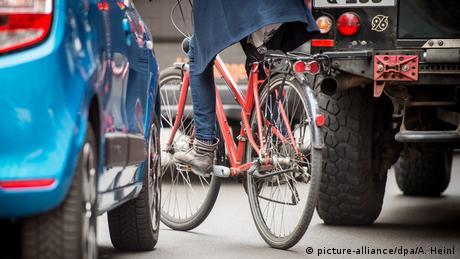 Велосипедист у Берліні лавірує на дорозі між двома автомобілями