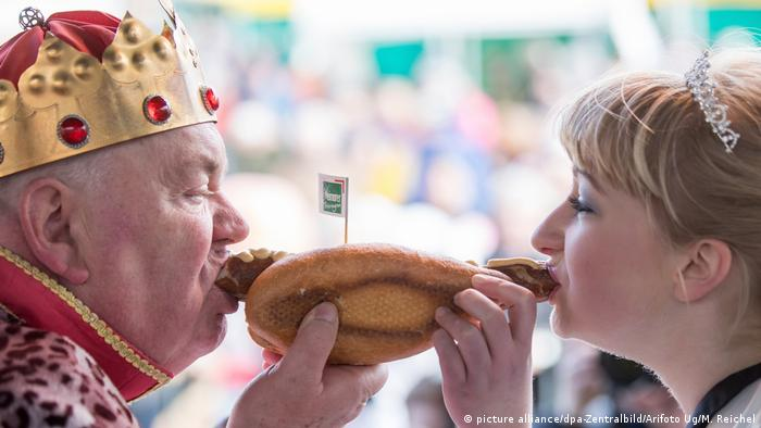 man and woman biting into a sausage in a roll (picture alliance/dpa-Zentralbild/Arifoto Ug/M. Reichel)