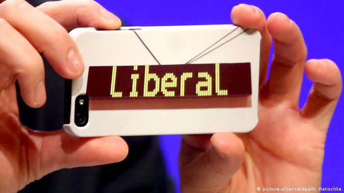 A person holds up a mobile phone on which the word liberal is written