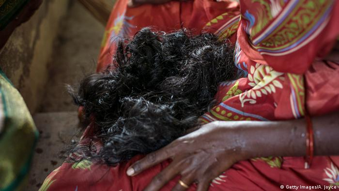 Indian woman holding her cut-off hair in her lap (Getty Images/A. Joyce)