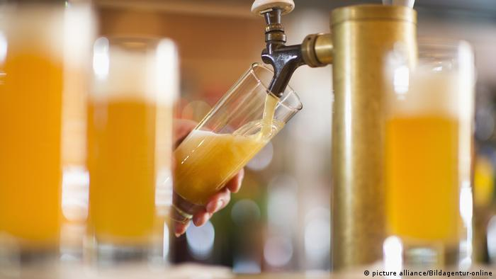 Barman poring beer from beer tap (picture alliance/Bildagentur-online)