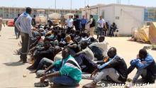ARCHIV - Afrikanische Migranten sitzen am 05.05.2015 in einer Basis der libyschenMarine inTripolis(Libyen). Sie wurden von einemBoot der libyschenMarine aus demMittelmeer gerettet. (Illustrationsfoto zu MINDS Global Spotlight - Menschenschmuggel vom 13.06.2017) Foto: Str/EPA/dpa +++(c) dpa - Bildfunk+++  