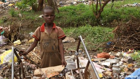 Senegal - Goldabbau - A young boy at a garbage site with a stream flowing behind him(DW/F. Annibale)